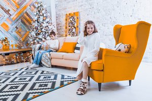 A 10-year-old girl sits on a yellow chair in the house before th