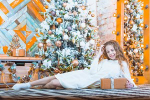 happy beautiful child girl with christmas present at home on the