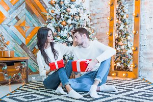 Young beautiful couple sitting near Christmas tree with xmas gif