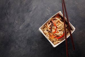 Close-up of noodles in a box with vegetables and beef in teriyaki sauce. Top view of Asian food, and wooden sticks. The concept of fast food. Copy space