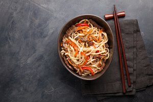 Close-up of noodles in a glass bowl with vegetables and beef in teriyaki sauce on a dark concrete background. Top view of Asian food, and wooden sticks. The concept of fast food. Copy space