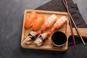 A set of sushi with salmon, shrimp and eel with a bowl of soy sauce and wooden chopsticks on a wooden Board. Delicious Japanese food on a dark stone background. Top view