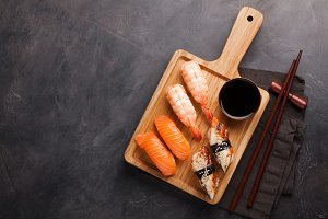 A set of sushi with salmon, shrimp and eel with a bowl of soy sauce and wooden chopsticks on a wooden Board. Delicious Japanese food on a dark stone background. Top view with copy space