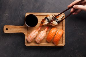 A set of sushi with salmon, shrimp and eel and wooden chopsticks on a wooden Board. Delicious Japanese food on a dark stone background. female hand takes the chopsticks in the sushi. Top view