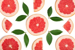 Grapefruit slices with leaves isolated on white background. Top view. Flat lay pattern