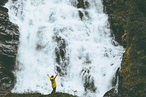 Woman raised hands at big waterfall
