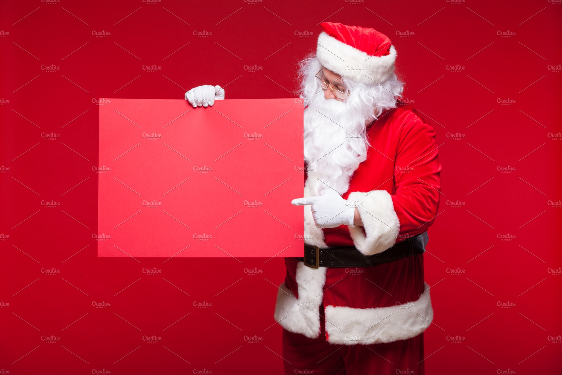 santa claus pointing in blank advertisement banner isolated on red - Santa Claus Red
