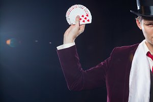 Midsection of magician showing fanned out cards against black background. Magician, Juggler man, Funny person, Black magic, Illusion close-up