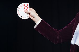 Hand with cards close-up. Midsection of magician showing fanned out cards against black background. Magician, Juggler man, Funny person, Black magic, Illusion