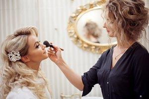 makeup artist preparing bride