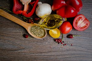 Olive oil, tomatoes and herbs on wooden table