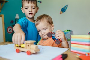 Boys playing together with toy cars