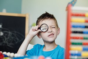 Boy playing with magnifying glass