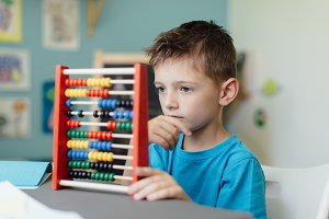 Boy learning maths with an abacus