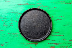 Empty rustic black cast iron plate over old wooden green background