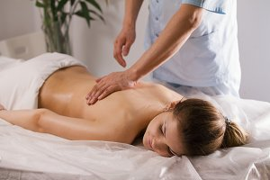 Blonde young woman model receiving relaxing massage in spa room