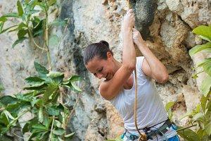 Woman rock climbing on white mountai