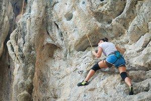 Woman rock climbing white mountain
