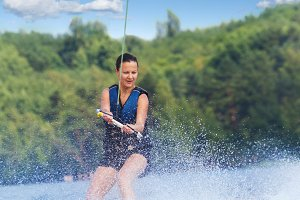 Woman wakeboarding on lake motorboat