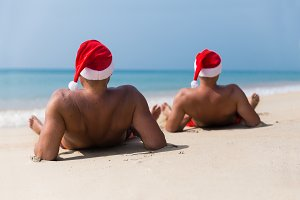 Two man in CHristmas hats on beach