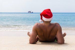 man in Christmas hat on beach party