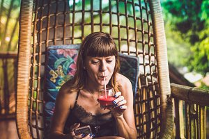 Beautiful woman drinking watermelon jucie while sitting on swing on the balcony of villa in the rainforest. Tropical island of Bali, Indonesia.