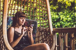 Beautiful woman using smartphone while sitting on swing on the balcony of villa in the rainforest. Tropical island of Bali, Indonesia.