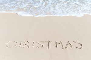 Christmas sign on the beach sand tropical hot winter concept