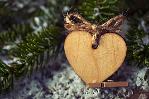 Christmas heart wooden shape with fir tree on wood