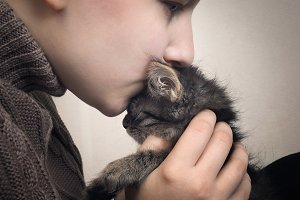 Girl kissing a little kitten