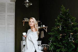 blonde in winter sweater has tea