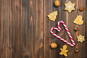 Christmas candy canes, gingerbreads of different shapes, hazelnuts, walnuts on a brown wooden table. Copy space.