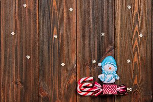 Christmas toys snowman on a sleigh of canes on a brown wooden table. Copy space.