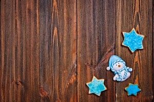 Christmas gingerbread cookies of blue star with Christmas-tree toys - snowman on brown wooden table. Copy space.