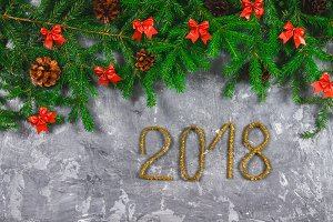 Fir branches with cones and red bows on top of a gray concrete background. New Year Christmas. Text 2018 of gold tinsel.