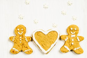 Gingerbread men friends near the heart on a white wooden table.