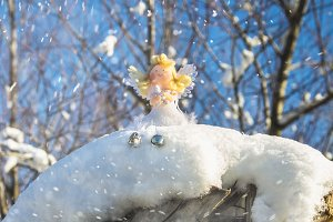 A fairy angel toy sits on the snow. Christmas toys.