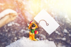 Toy dog with a white blank sheet - a symbol of the new year in the snow. Christmas toys.