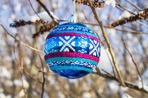 A blue New Year ball hangs on a branch with snow. Christmas toys.