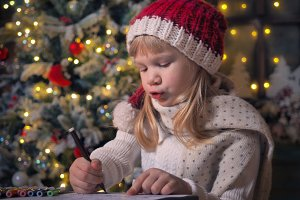 Child writes letter Santa Claus.
