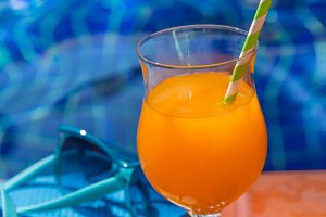 Glass of orange juice drink fresh with flowers, sunglasses and s