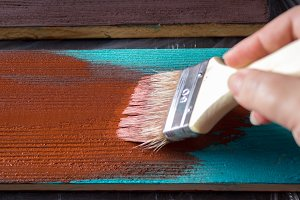 Brush with paint in hand. A man paints blue boards in a brown paint brush.