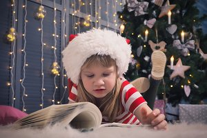 Little girl in Christmas hat reading a book