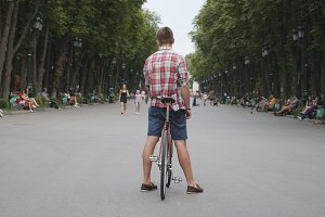 Rear view of young man with bicycle on path in city park. Unrecognizable guy standing with fixed gear bike in city street. Close up of white wheels of retro bicycle with stylish man. Healthy lifestyle