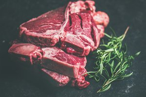 Raw beef meat t-bone steaks with rosemary on black background