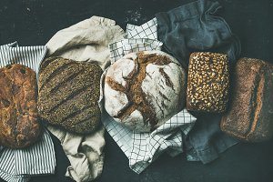 Various bread selection flat-lay, black background