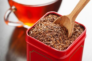 Rooibos in tea tin box and tea cup