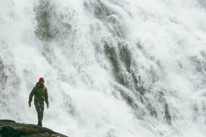 Man tourist hiking at big waterfall