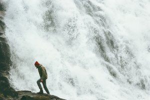 Man walking at big waterfall outdoor