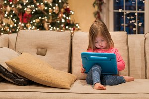 Preschool girl using a tablet computer at home at Christmas